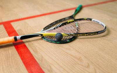 Squash game equipment closeup view. Rackets and ball on the floor in indoor training club